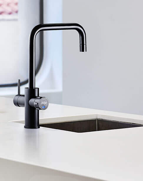 Black Celsius Cube Tap next to a kitchen sink